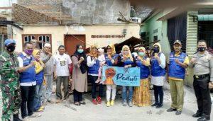 Sekretaris Umum IKA SMEAN2/SMKN6 Medan Sulastri saat menyerahkan bantuan kepada Kepling 05 Khairil Amri Nasution dilokasi kebakaran Jalan Bliton Barat, Belawan.